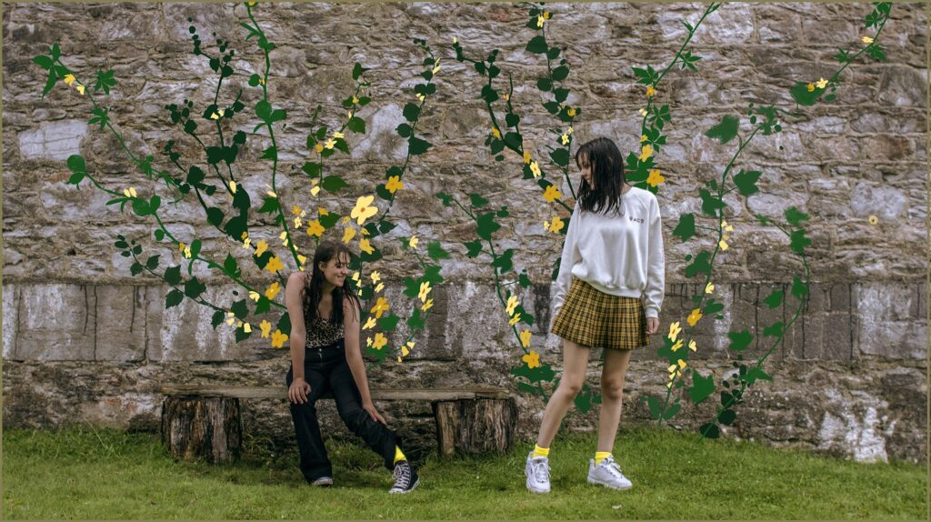 Two teenage girls pass each other in front of an old wall. They are so delighted to see they are both wearing yellow socks, that the wall spontaneously blossoms with beautiful yellow flowers.