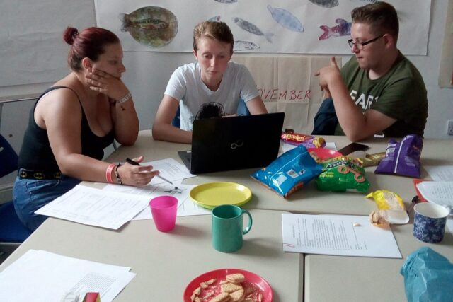 Three people sat at a table, with a laptop, papers and snacks